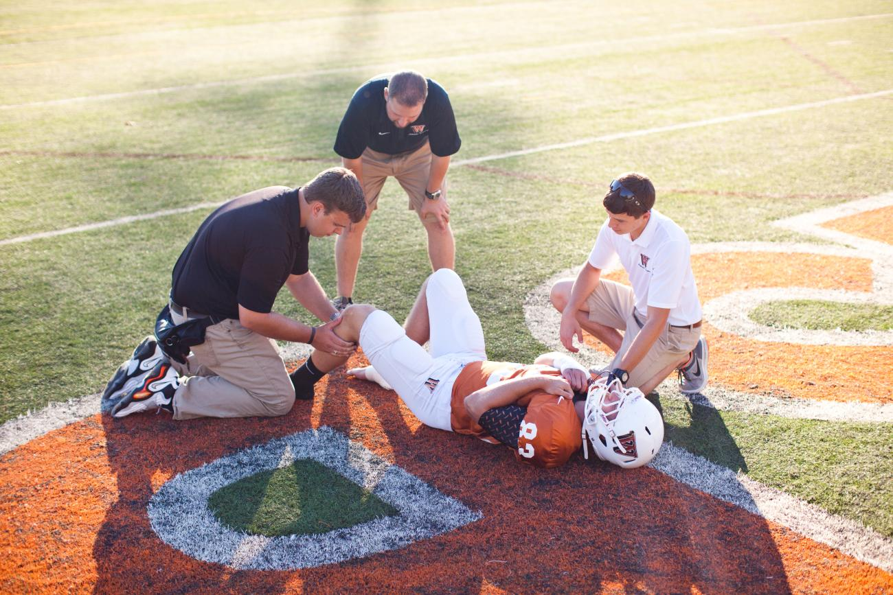 Athletic trainers with a football player